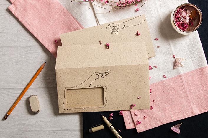 Karte und Hülle aus Graspapier in einem Flatlay. Durch die Illustration reichen sich die Beiden die Hand.