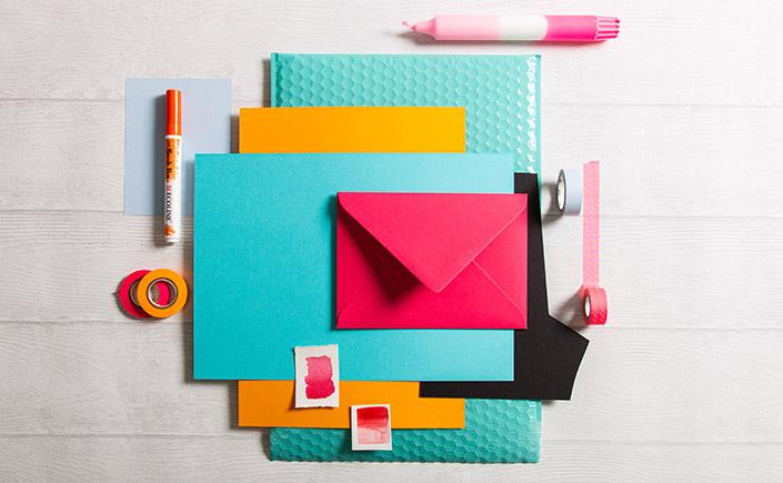 Flatlay Foto mit türkisen und orangen Papieren rund um eine Colorplan B6 Hülle in der Farbe Hot Pink.