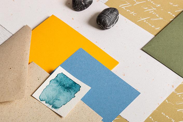 Detailfoto von Graspapierumschalg und blauen sowie orangen Papieren aus der herbstlichen Farbpalette.