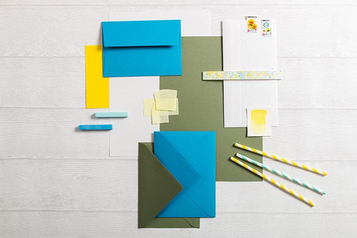 Flatlay Foto einer sommerlichen Farbpalete mit Papieren in Olivgrün, Sonnengelb und hellem Blau.