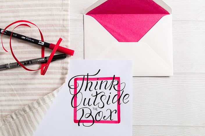 Lettering in schwarz und pink auf DCP Papier mit einem passenden weißen Umschlag mit pinkem Inlay