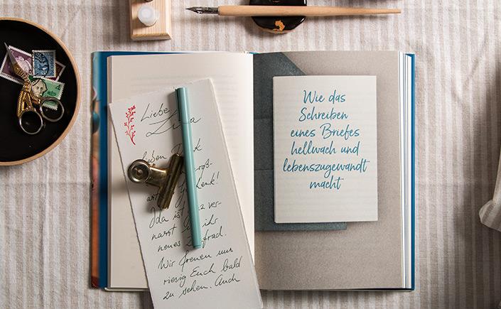 """Flatlay des aufgeschlagenen Buches """"Die fast vergessene Kunst des Briefeschreibens"""" von Gaby Trombello-Wirkus und Titus Müller."""