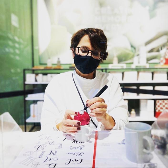 Gaby Trombello-Wirkus beschriftet eine rote Weihnachtskugel mit Handlettering