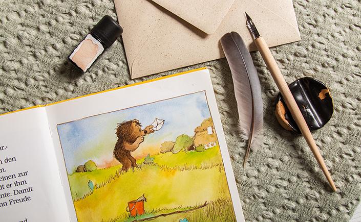 """Detailaufnahme einer Seite aus dem Buch """"Post für den Tiger"""" neben Schreibfeder und Graspapier Briefhülle"""