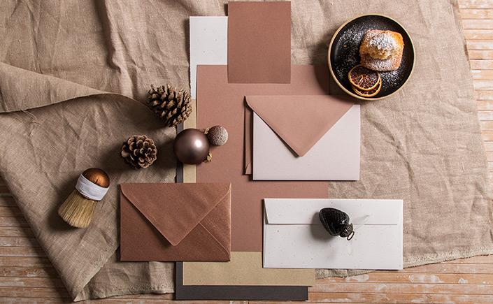 Weihnachtliches Stimmungsbild mit einem Mandeltörtchen, Tannenzapfen, Baumkugeln und Papieren aus der Farbpalette Crush Almond.