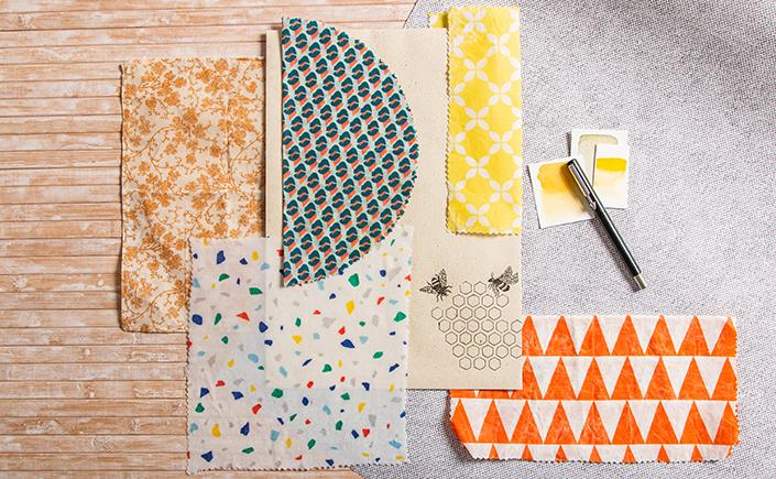 Flatlay von bunten Bienenwachstüchern rund um eine C4 Graspapier Hülle mit Illustration