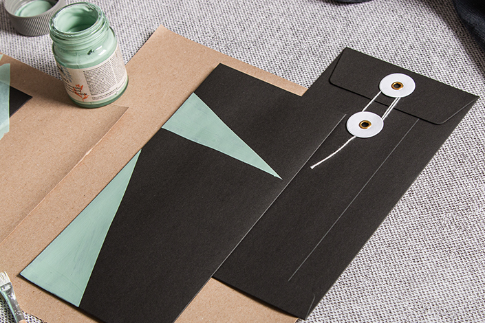 zwei schwarze Hüllen mit Bindfadenverschluss werden mit Kreul Nature Farben bemalt.