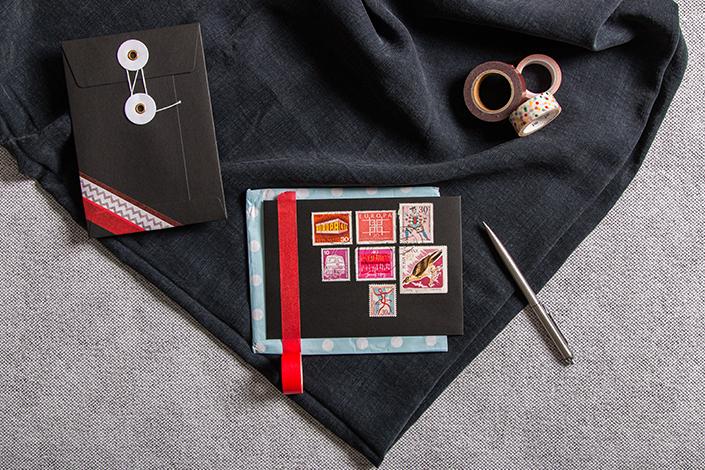 Collage roter Briefmarken auf einer schwarzen Briefhülle mit Bindfadenverschluss