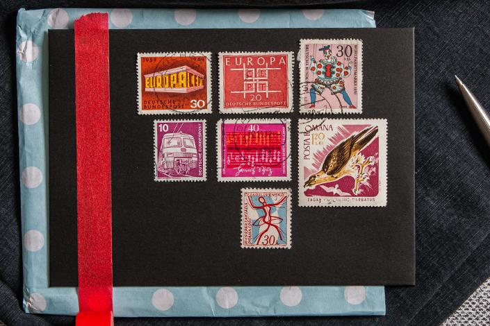 Collage roter Briefmarken auf einem schwarzen Briefumschlag mit Bindfadenverschluss.